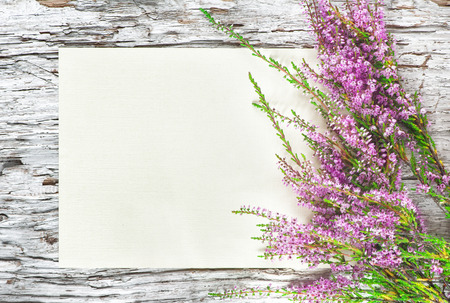 Old rough wooden background with paper and heather