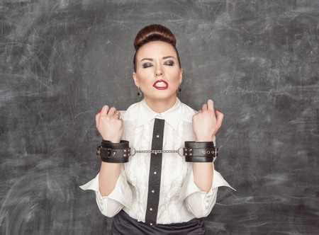 Business woman with handcuffs on the blackboard background