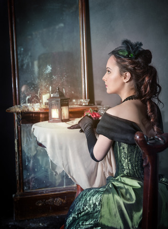 Beautiful young woman in green medieval dress sitting near mirror