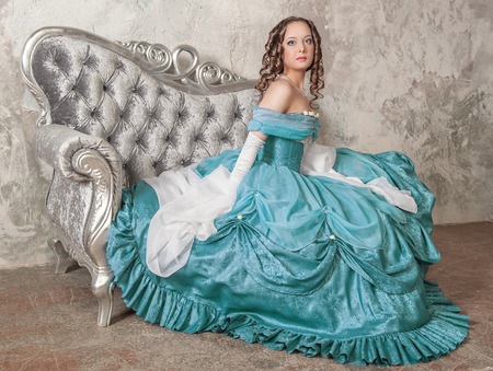 Beautiful young woman in blue medieval dress on the sofa