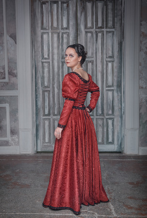 Beautiful young woman in red long medieval dress