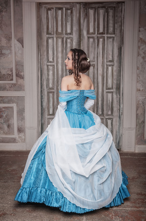 Beautiful young woman in blue long medieval dress