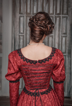 Portrait of young beautiful medieval woman in red dress, back
