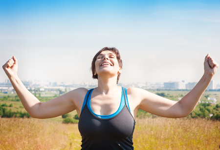 Happy beautiful successful plus size woman raising arms to the sky outdoor in summer