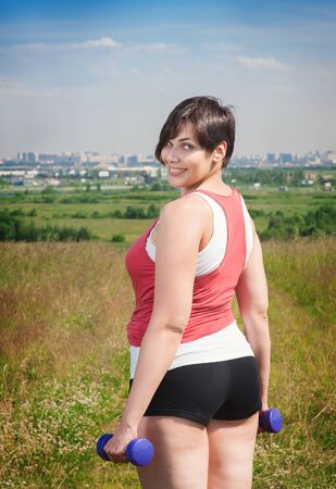 Beautiful plus size woman exercising with dumbbells outdoor