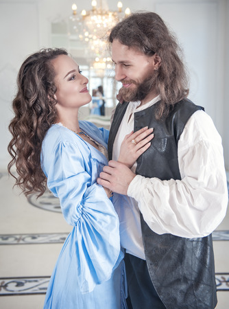 Beautiful couple woman and man in medieval clothes in the room