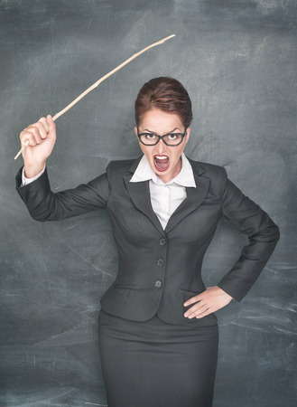 Angry teacher with wooden stick on chalkboard background