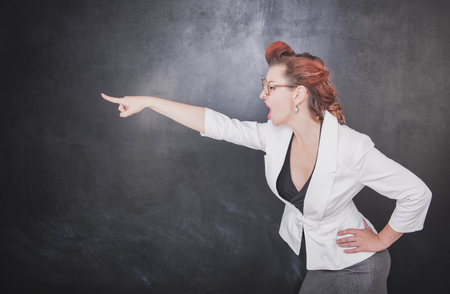 Angry screaming teacher pointing out on chalkboard blackboard background