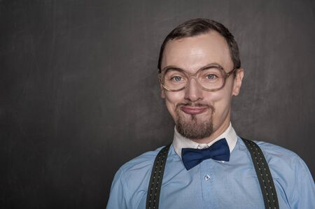 Foto de Funny teacher in eyeglasses smiling on blackboard background - Imagen libre de derechos