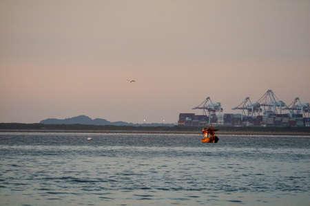 Photo pour sunset fisging boat on sea and seaport background - image libre de droit