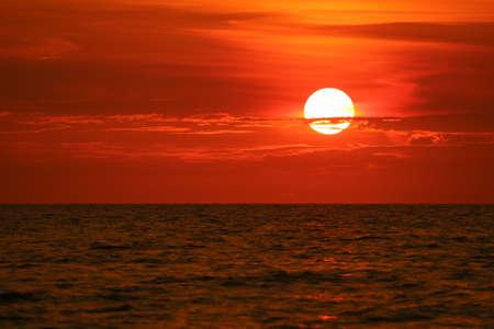 Foto de sun back on sunset sky horizon and wave on surface sea - Imagen libre de derechos