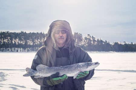 Photo pour man holding catch winter fishing pike fish - image libre de droit
