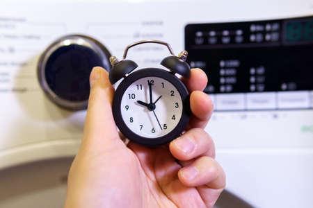 Foto de Washing clothes. Time to wash your dirty laundry. alarm clock in hand selective focus - Imagen libre de derechos