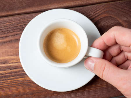 Photo pour close-up of a man's hand holding a small white cup of aromatic espresso over a white saucer. Wooden background, Top view, flat lay - image libre de droit