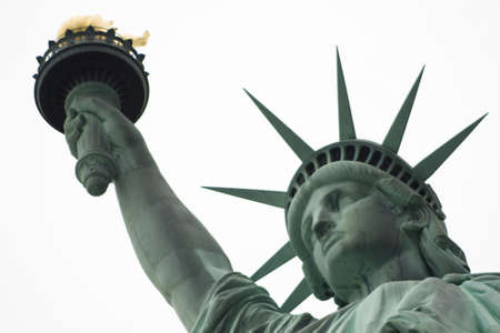 Close up of the Statue of Liberty head, arm and flame on a white sky background