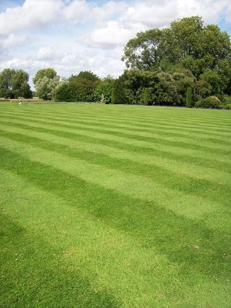 Photo of a garden with striped lawn and trees in the distance