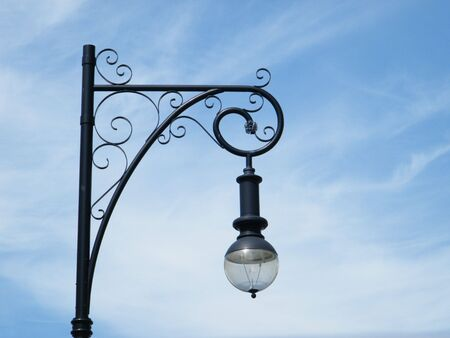 Isolated ornate street light against a blue sky background