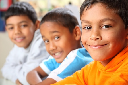 Photo pour Row of three smiling young school boys in class - image libre de droit