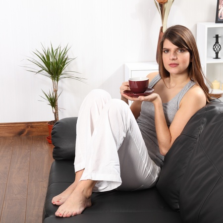 Beautiful young, caucasian woman, sitting on the sofa at home drinking coffee. She is wearing white linen trousers and a grey vest.