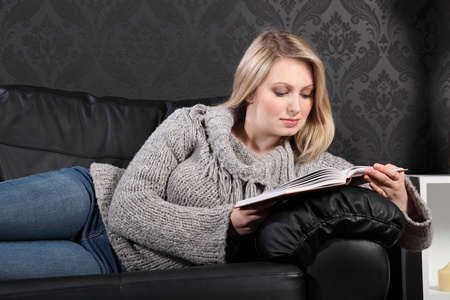 Quiet time for beautiful young blonde woman sitting reading a book on black leather sofa at home, wearing casual grey knitted sweater, blue jeans and just relaxing.