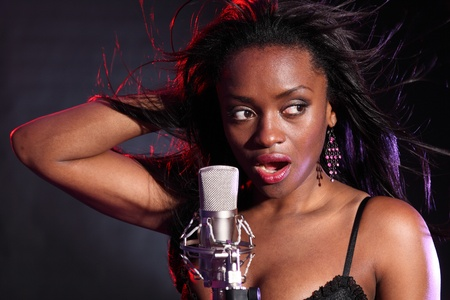 Beautiful african american girl on stage with microphone singing. Her hair is blowing back with wind effect and lit with red and blue lighting.