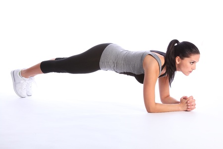 Fit beautiful young woman concentrates during floor exercise during fitness workout. She is wearing a grey and black sports outfit with white trainers.