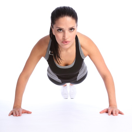 Fit beautiful and young athletic woman doing push up exercises on floor, wearing a grey and black sports outfit.