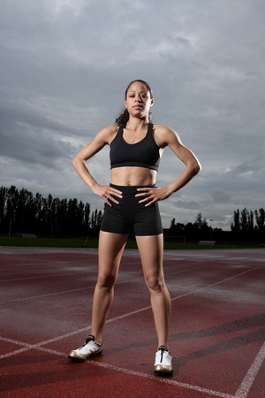 Beautiful fit young female athlete standing on running track wearing black lycra sports outfit and running spikes. Grey cloudy sky in background.