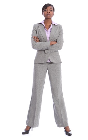 Serious and confident young african american business woman, full length shot standing in grey suit with arms folded.