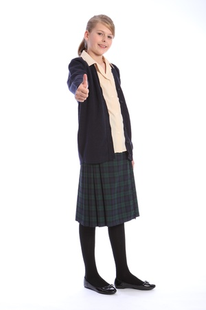 Thumbs up success with a smile from beautiful teenage high school student girl wearing school uniform, tartan skirt and beige shirt with navy cardigan.
