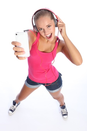 Dancing to music on her cell phone a teenage girl wearing denim shorts and pink top looks up singing with big happy excited expression.
