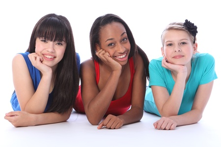 Teenage school student best friends lying on the floor together made up of mixed race african american, oriental Japanese and caucasian all with happy smiles having a laugh.