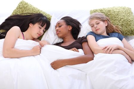 Falling asleep at slumber party for three tired beautiful teenage girl friends, a mixed race african american, oriental Japanese and blonde caucasian school mates.