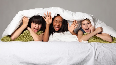 Hilarious fun and scream with laughter at sleepover party for three happy beautiful teenage girl friends, a mixed race african american, oriental Japanese and blonde caucasian school mates.