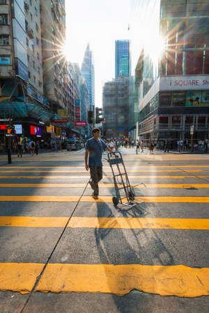 Photo pour Hong Kong - October 3, 2019: A man bringing trolley at crossing under the sunlight. - image libre de droit