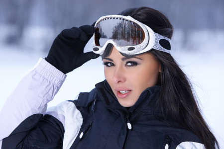 Photo pour Beautiful woman wearing goggles in snowy winter outdoors - image libre de droit