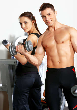 Foto de Sporty couple exercising at the fitness gym - Imagen libre de derechos