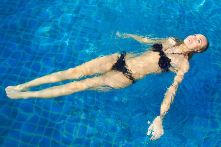 Smiling beautiful woman in a bikini lying on her back floating in a pool relaxing in the warm summer sunshine