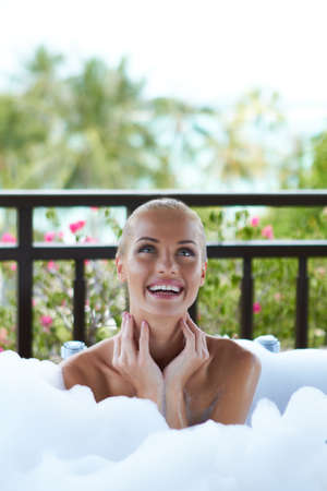 Pretty smiling woman sitting enjoying a foamy bubble bath looking upwards off camera