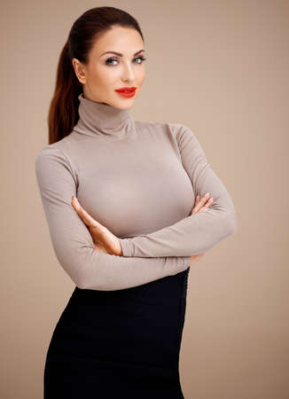 Beautiful shapely glamorous professional woman with her hair tied neatly back standing with her arms folded looking at the camera on a beige background