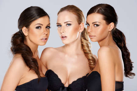 Three sensual beautiful beguiling young women wearing black lingerie looking seductively at the camera as they pose together in a group