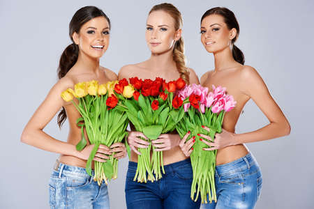 A trio of beautiful young women holding bouquets of fresh spring tulips in front of their chests as they smile at the camera