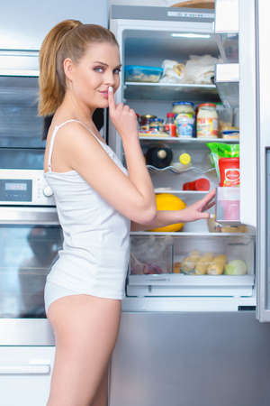 Young woman snacking from her refrigerator turning to smile at the camera with her finger raised to her lips in a hush gesture as she asks for secrecy