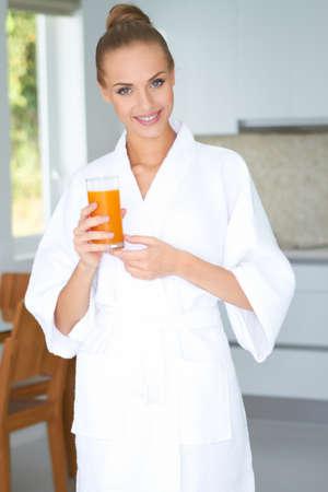 Woman in bath robe drinking orange juice