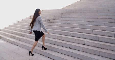 Foto de Serious young business woman in high heel shoes walking up long flight of marble stairs outdoors - Imagen libre de derechos