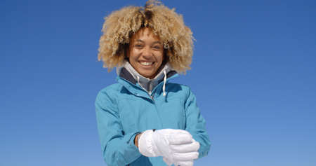 Cute young single woman in frizzy hair and winter coat with thick white ski gloves under clear blue skyの写真素材