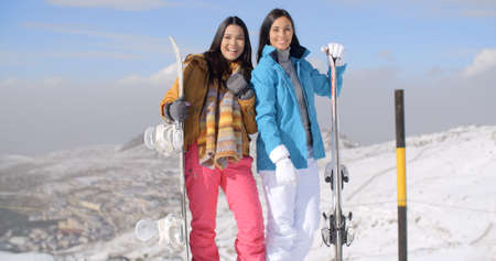 Two attractive happy young woman with their snowboards standing posing and smiling at the edge of a run on a mountain ski resort with copy space.