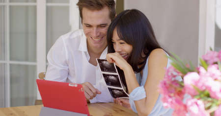 Happy young adult man and woman showing off ultrasound pictures of baby in womb to someone through a video chat on their tablet computerの写真素材