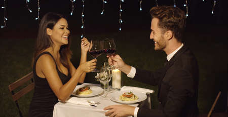 Photo pour Happy loving couple toasting each other during a romantic dinner as they celebrate their love - image libre de droit