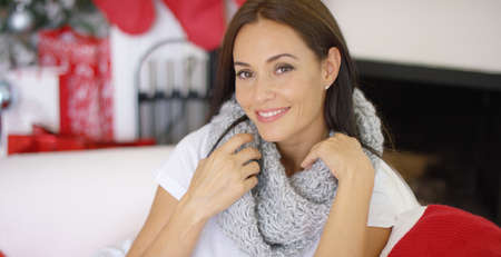 Beautiful sincere young woman wearing a warm soft winter scarf as she relaxes at home in a decorated living room celebrating Christmas